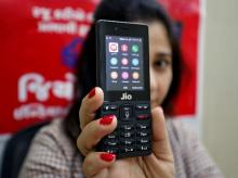 A sales person displays JioPhone as she poses for a photograph at a store of Reliance Industries' Jio telecoms unit, on the outskirts of Ahmedabad. (File Photo: Reuters)