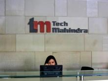 In this file photo, an employee sits at the front desk inside Tech Mahindra office building in Noida on the outskirts of New Delhi. (Photo: Reuters)