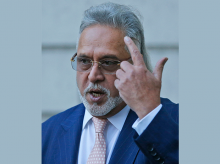 F1 Force India team boss Vijay Mallya waits outside Westminster Magistrates Court in London