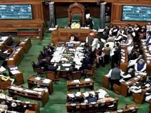 Opposition members protest inside the Lok Sabha in New Delhi during the ongoing winter session of Parliament