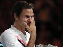 Roger Federer wipes tears away from his eyes as he holds his trophy after defeating Croatia's Marin Cilic during the men's singles final at the Australian Open. Photo: Reuters