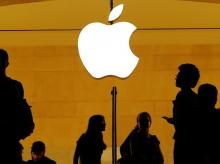 Customers walk past an Apple logo inside of an Apple store at Grand Central Station in New York | File Photo: Reuters