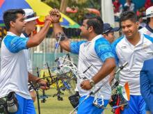 Indian archers Rajat Chauhan, Aman Saini and Abhishek Verma celebrate after scoring points in men's compound team event, at the Asian Games 2018. Photo: PTI
