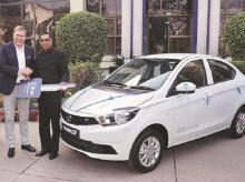 Tata Motors MD & CEO Guenter Butschek (left) hands over a symbolic key of Tigor EV to EESL MD Saurabh Kumar in 2017