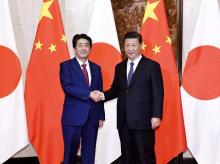 Japanese Prime Minister Shinzo Abe, left, poses with Chinese President Xi Jinping