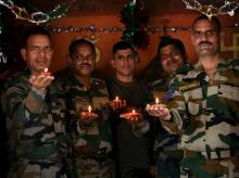 Army soldiers hold earthen lamps near the LoC as they celebrate Diwali festival in Sunderbani district