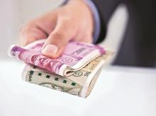Rupee settles below 70 after three months, crude oil slides further