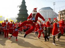 People dance before the annual Santa Claus city race in Skopje, Macedonia