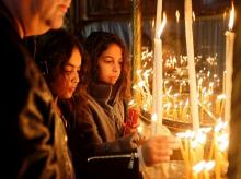 Girls light candles at the Church of the Nativity, in Bethlehem in the Israeli-occupied West Bank