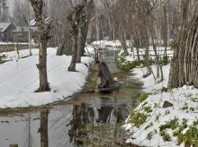 A local takes his boat through an area covered by snow on a cold, winter morning, in the interiors of Dal Lake in Srinagar