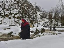 A woman walks on a snow-covered path during light rains on the outskirts of Srinagar
