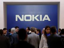 Visitors stand next to a logo of Nokia at Mobile World Congress in Barcelona, Spain