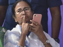 West Bengal Chief Minister Mamata Banerjee gestures as she speaks on her mobile  during a sit-in over the CBI's attempt to question the Kolkata Police commissioner in connection with chit fund scams, in Kolkata. Photo: PTI