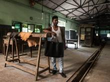 One of the workers from Chamar Studio poses with the bag that he made