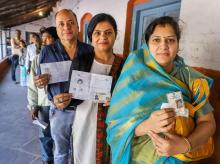 Ppeople wait with their identity cards to cast their votes for the Madhya Pradesh assembly elections. Photo: PTI