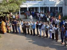 People wait with their identity cards to cast their votes for the Madhya Pradesh assembly elections. Photo: PTI