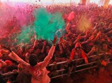 Devotees play with 'gulal' on the occasion of Holi festival celebrations at Govind Dev Ji temple, in Jaipur