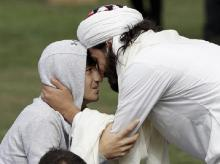 Muslim men embrace during Friday prayers at Hagley Park in Christchurch | Photo: Reuters