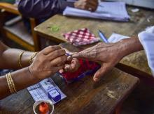 A polling officer puts an indelible ink mark on the finger of a voter during the second phase of the general elections, at a polling station, in Nagaon, Thursday, April 18, 2019 | Photo: PTI