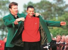 A 21-year-old Woods receiving his first Green Jacket from Nick Faldo in 1997. Photo: Reuters