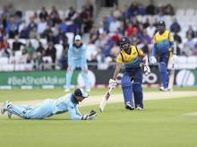 Sri Lanka's Kusal Mendis successfully makes a run, as England's wicketkeeper Jos Buttler fields the ball