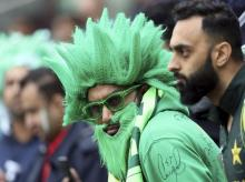 A Pakistan fan wait as rain is expected to slightly delay the start of play during the Cricket World Cup match between New Zealand and Pakistan at the Edgbaston Stadium in Birmingham