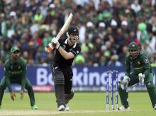 New Zealand's batsman James Neesham, middle, reacts after playing a shot as Pakistan's captain Sarfaraz Ahmed, right and teammate watches on