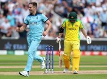 England's Chris Woakes, left, celebrates the dismissal of Australia's David Warner