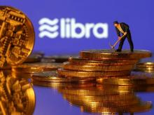 A small toy figure stands on representations of virtual currency in front of the Libra logo in this illustration picture. Photo: Reuters