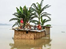 A family marooned on the top of a hut in the flood-hit locality of Panikhaiti in Kamrup district of Assam