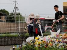 People pray in front of a row of flowers placed for victims of the torched Kyoto Animation building on Saturday.  Photo: Reuters