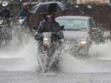 A biker drives through a waterlogged street during heavy monsoon rain at Kings Circle, in Mumbai