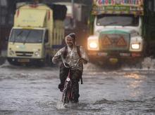 A cyclist rides through a waterlogged street during heavy monsoon rain at Kings Circle, in Mumbai
