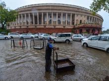 A worker stands on a waterlogged street at Parliament after heavy rain, in New Delhi