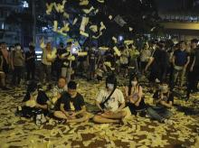 Hong Kong: Protesters sit as joss papers are tossed during a demonstration that coincided with the ghost festival, a traditional local observance marked by the belief that the gates of hell will open for the month and ghosts would roam the streets, i