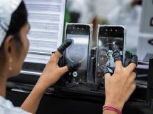 An employee tests the camera of a mobile phone. (Photographer: Karen Dias/Bloomberg)