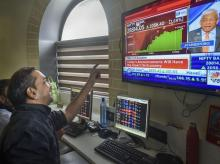 Investors react as they watch the stock prices on a digital screen, at BSE building in Mumbai