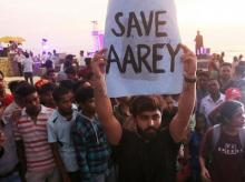 Mumbai: An activist holds a placard during a protest against cutting down of trees for a proposed metro car shed project at Aarey Colony in Mumbai, Sunday, Oct. 6, 2019. (PTI Photo)