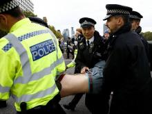 Police officers detain an activist at Westminster Bridge during the Extinction Rebellion protest in London, Britain. Photo: Reuters
