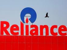 FILE PHOTO: A bird flies past a Reliance Industries logo installed on its mart in Ahmedabad. Photo: Reuters