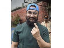 Bollywood actor Aamir Khan shows his finger marked with indelible ink after casting vote during the Maharashtra Assembly elections, in Mumbai