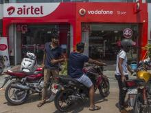 Motorcyclists park their bikes outside a Bharti Airtel Ltd. and a Vodafone India Ltd. stores in New Delhi
