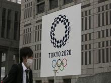 A man walks past a large banner promoting the Tokyo 2020 Olympics in Tokyo. Photo: AP | PTI