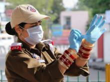 A policewoman wears gloves as she stands to perform her duty, during a nationwide lockdown, imposed in the wake of coronavirus pandemic, in Jammu. Photo: PTI