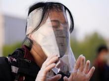 A traveller adjusts her face shield outside Hankou Railway Station. Photo: Reuters