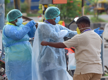 Civil defence officials wear protective suits to help a man who was lying on the roadside near Hebbal flyover during a nationwide lockdown imposed in the wake of novel coronavirus pandemic, in Bengaluru. Photo: PTI