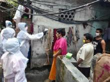 Health workers conducting door-to-door thermal screening at a slum area to detect COVID-19 positive cases in Kolkata. Photo: PTI
