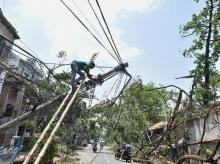 A worker attempts to repair an electric pole, in the aftermath of Cyclone Amphan, in Kolkata