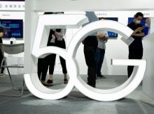 Visitors wearing mask to protect from the coronavirus walk past a 5G sign at the China Beijing International High Tech Expo in Beijing, China
