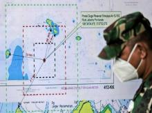 An Indonesian soldier walks past a map showing the location where a Sriwijaya Air passenger jet has lost contact with air traffic controllers shortly after taking off,
